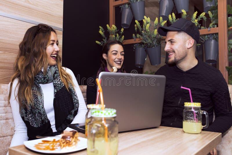 Glimlachende vrienden die laptop met behulp van royalty-vrije stock foto's