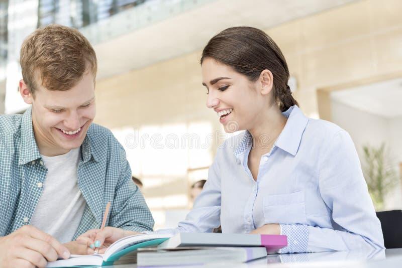 Glimlachende vrienden die over boek bespreken terwijl het zitten bij lijst in bibliotheek royalty-vrije stock foto