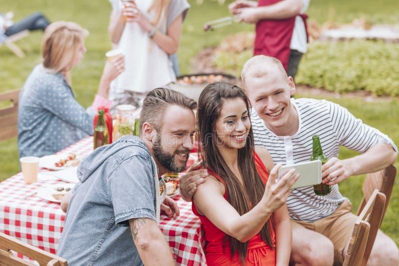 Glimlachende vrienden die selfie tijdens grillpartij nemen in de tuin royalty-vrije stock fotografie