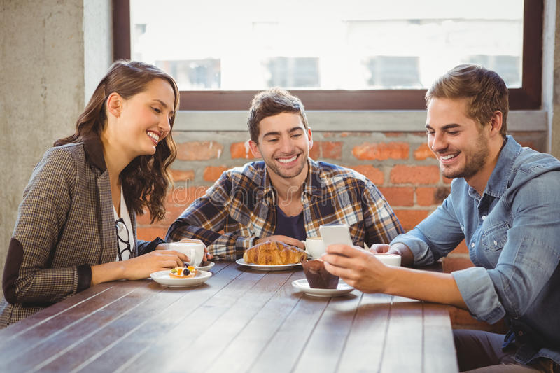 Glimlachende vrienden die smartphone bekijken royalty-vrije stock afbeeldingen