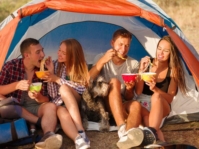 Glimlachende vrienden die snel voedselnoedels op een het kamperen reis eten Wandelaars die op een tentachtergrond eten Actief vak stock foto's