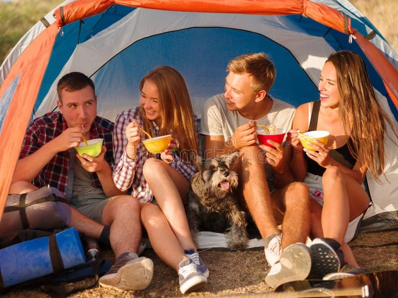 Glimlachende vrienden die snel voedselnoedels op een het kamperen reis eten Wandelaars die op een tentachtergrond eten Actief vak royalty-vrije stock fotografie