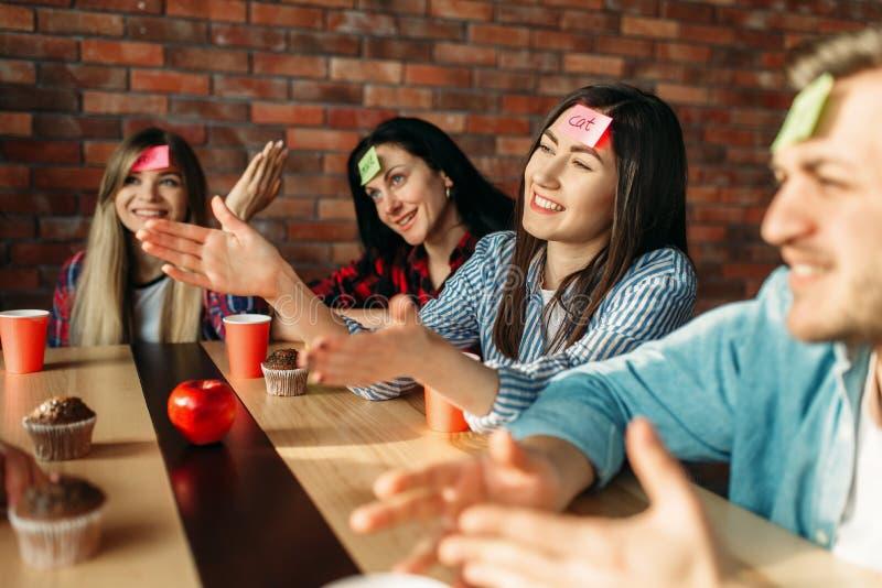Glimlachende vrienden die stickernota's spelen aan voorhoofd stock foto's