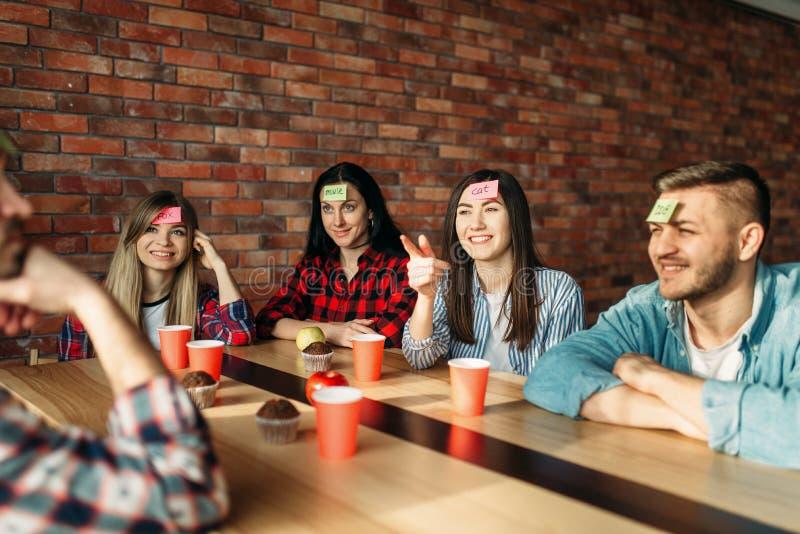 Glimlachende vrienden die stickernota's spelen aan voorhoofd royalty-vrije stock foto