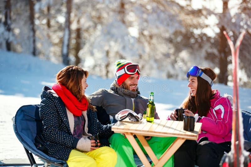 Download Glimlachende Vrienden Die Tijd Samen En Drank Na Binnen Het Ski?en Doorbrengen Stock Foto - Afbeelding bestaande uit gelukkig, heet: 107707516