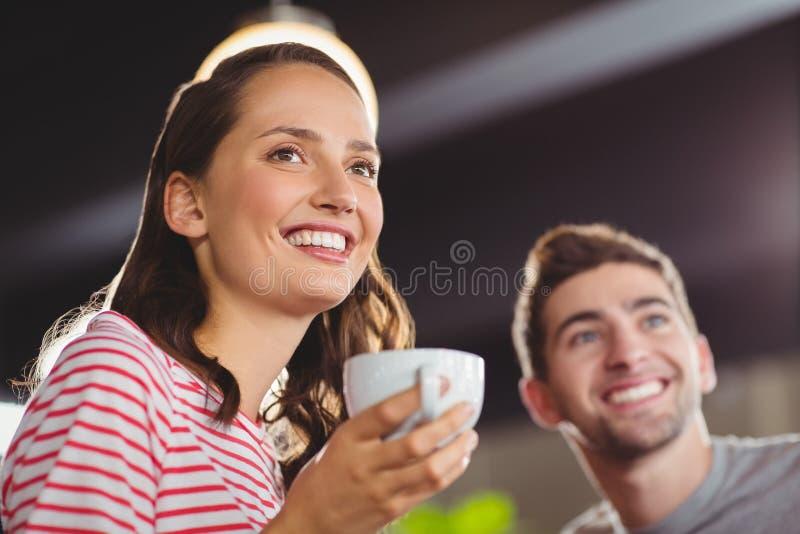 Glimlachende vrienden die van koffie samen genieten stock foto
