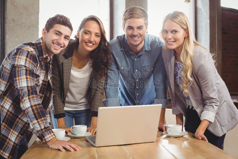 Glimlachende vrienden die zich rond laptop bevinden stock foto's
