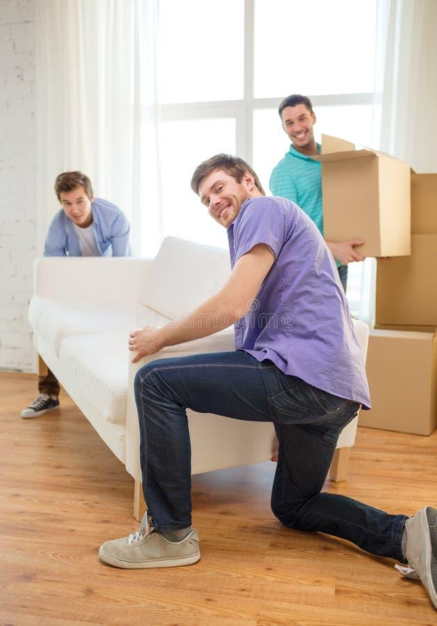 Glimlachende vrienden met bank en dozen bij nieuw huis royalty-vrije stock afbeelding