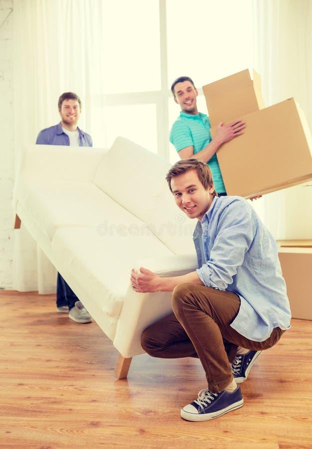 Glimlachende vrienden met bank en dozen bij nieuw huis stock foto