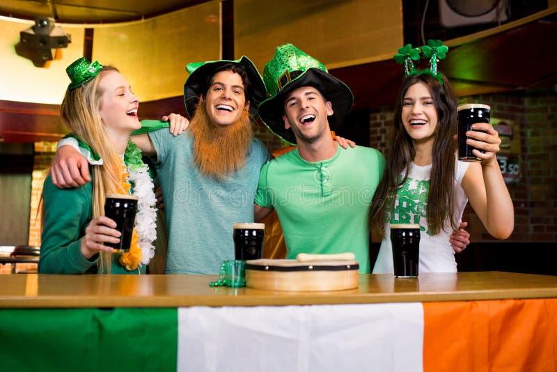Glimlachende vrienden met Ierse toebehoren stock foto