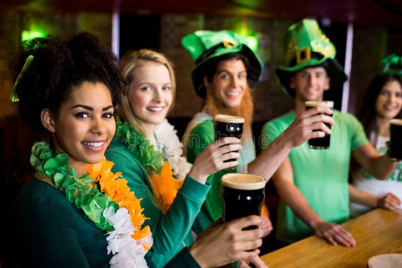 Glimlachende vrienden met Ierse toebehoren stock foto's
