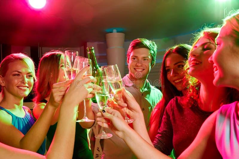 Glimlachende vrienden met wijnglazen en bier in club royalty-vrije stock afbeeldingen