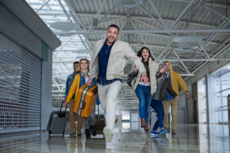 Glimlachende vrienden met zakken die zich omhoog voor een vlucht haasten stock afbeeldingen
