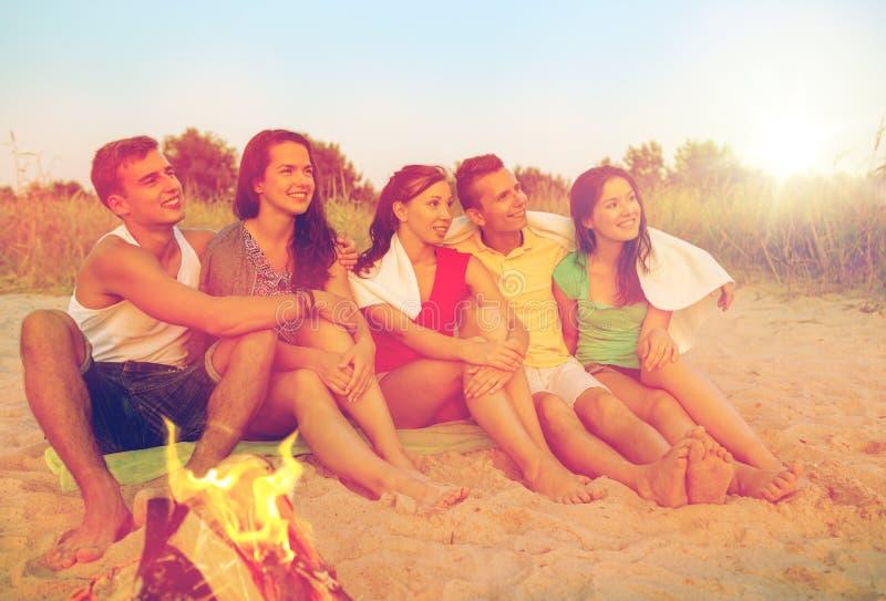 Glimlachende vrienden in zonnebril op de zomerstrand stock afbeelding
