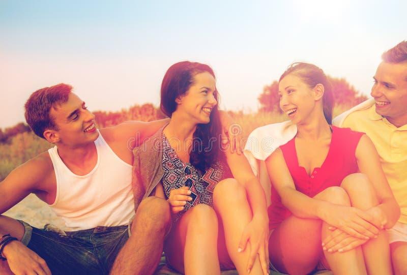 Glimlachende vrienden in zonnebril op de zomerstrand royalty-vrije stock afbeelding