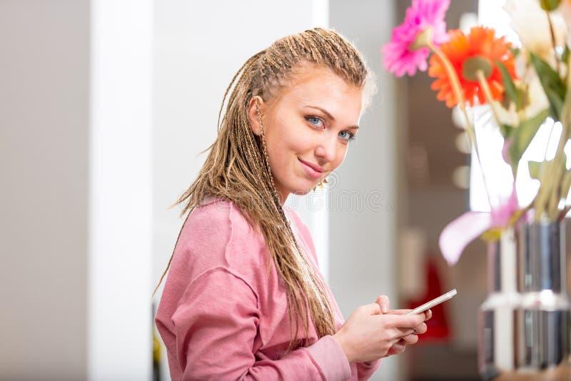 Glimlachende vriendschappelijke jonge vrouw die mobiel gebruiken royalty-vrije stock afbeelding