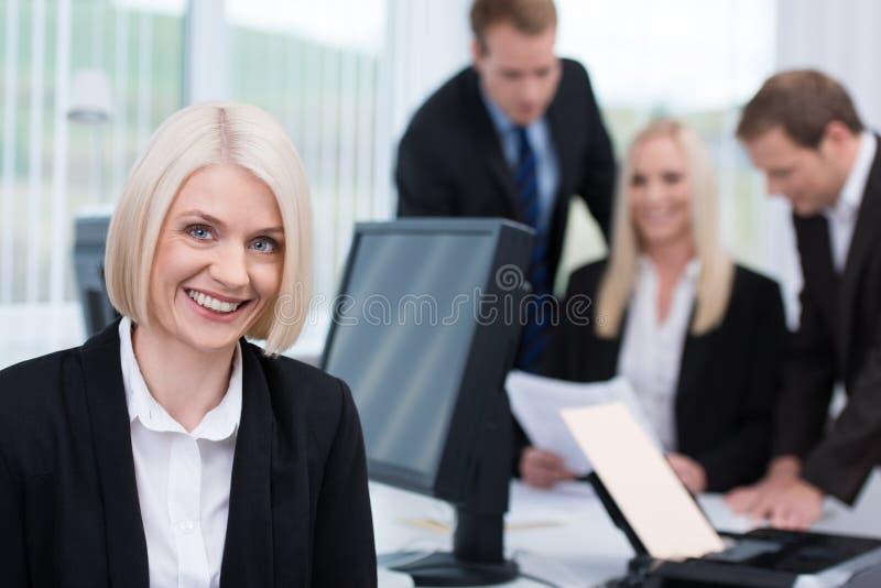 Glimlachende vriendschappelijke onderneemster in het bureau royalty-vrije stock fotografie