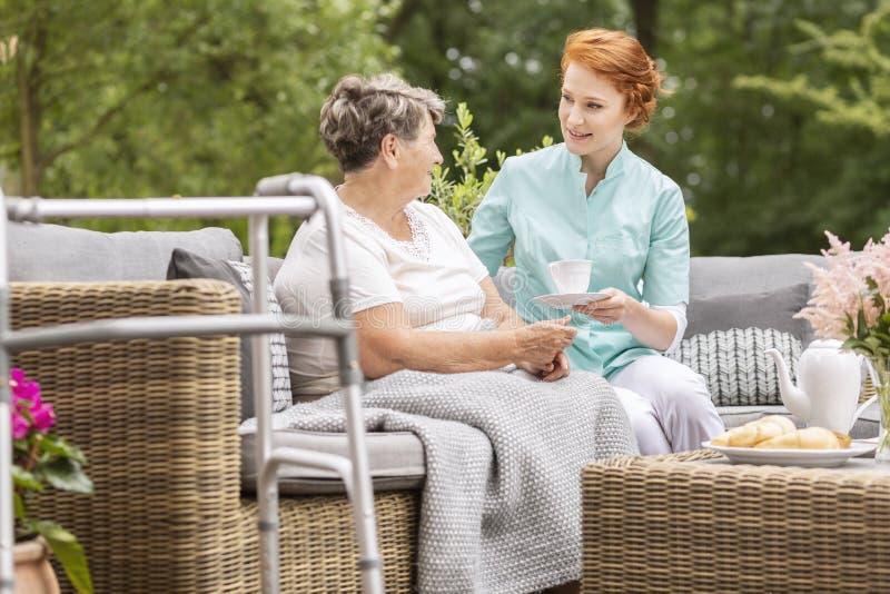 Glimlachende vriendschappelijke verpleegster die thee geven aan bejaarde op terrac royalty-vrije stock foto's
