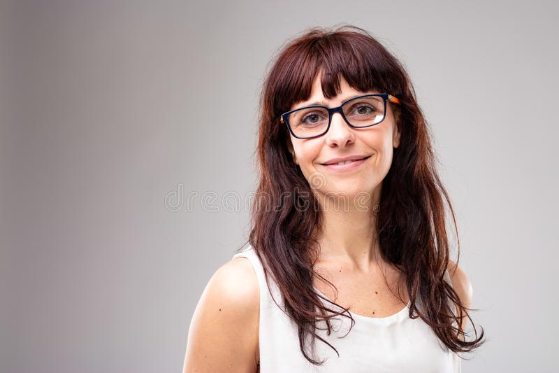 Glimlachende vriendschappelijke vrouw die glazen dragen stock afbeeldingen