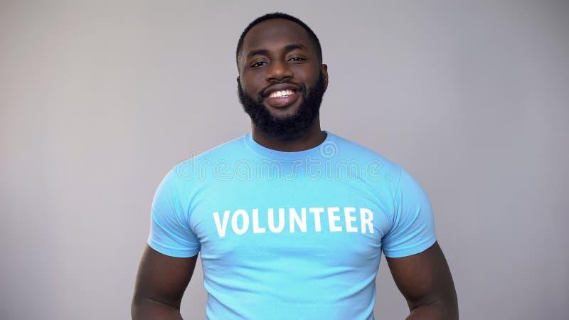 Glimlachende vrijwilliger Afrikaans-Amerikaan die in blauwe t-shirt camera, hulp bekijken royalty-vrije stock afbeeldingen