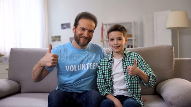 Glimlachende vrijwilliger en schooljongen die op middelbare leeftijd duim-omhoog aan camera, advertentie tonen stock foto's