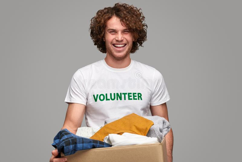 Glimlachende vrijwilliger met klerenschenkingen royalty-vrije stock fotografie