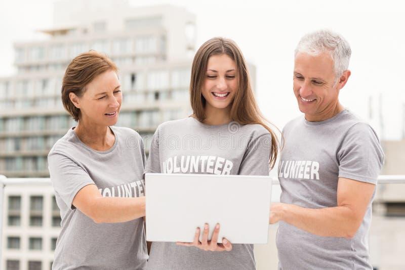 Glimlachende vrijwilligers die laptop samen met behulp van royalty-vrije stock foto