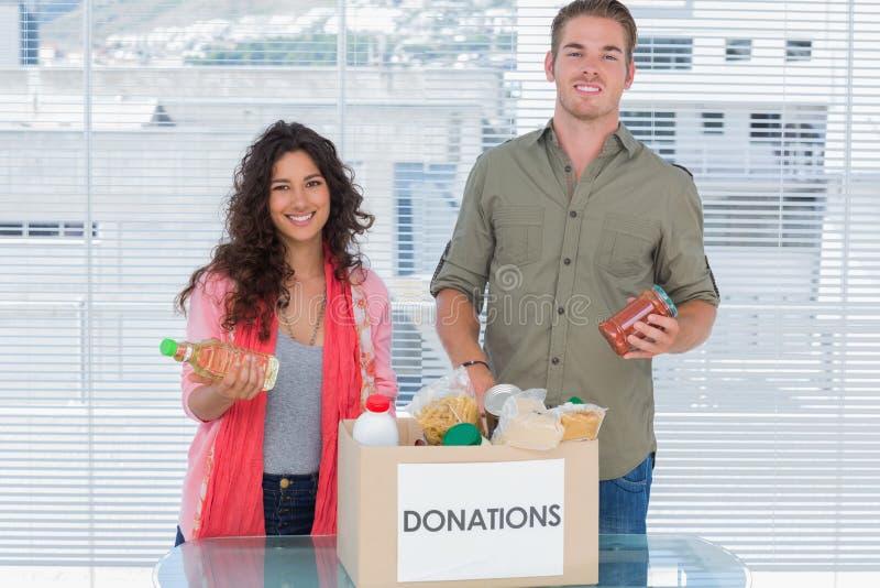 Glimlachende vrijwilligers die voedsel van schenkingendoos nemen stock foto