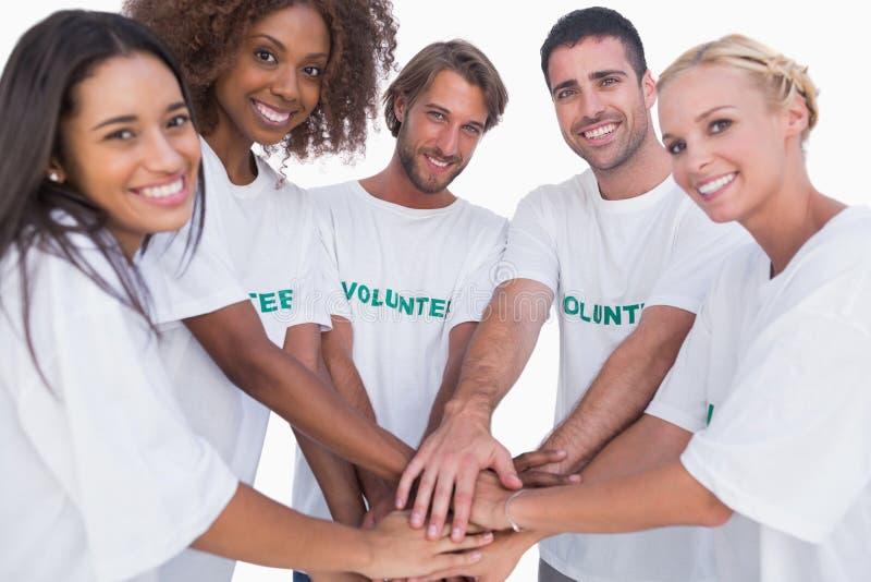 Glimlachende vrijwilligersgroep die handen samenbrengen stock foto's