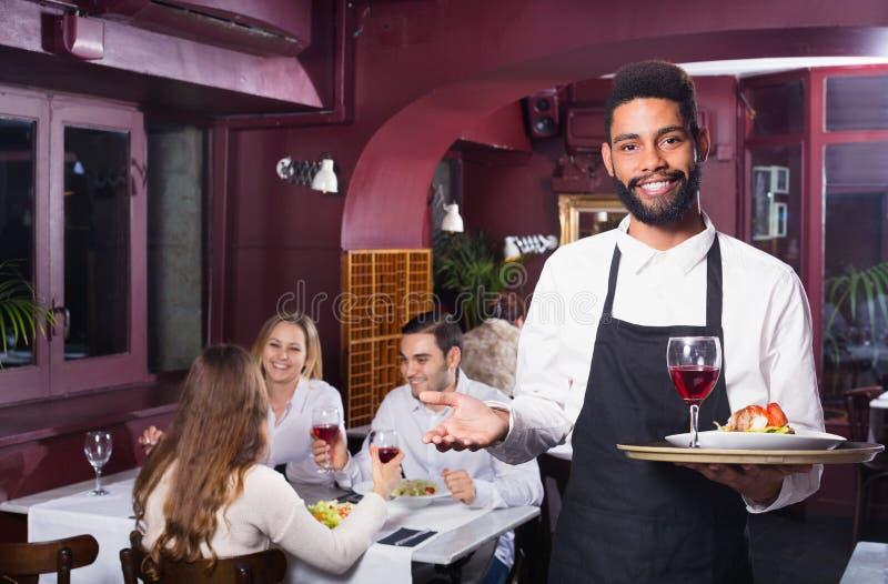 Glimlachende vrolijke kelner die volwassenen behandelen royalty-vrije stock foto's