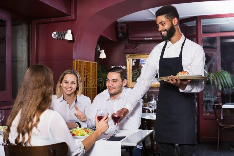 Glimlachende vrolijke kelner die volwassenen behandelen royalty-vrije stock afbeeldingen