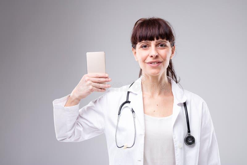 Glimlachende vrouw arts die mobiel haar steunen stock foto