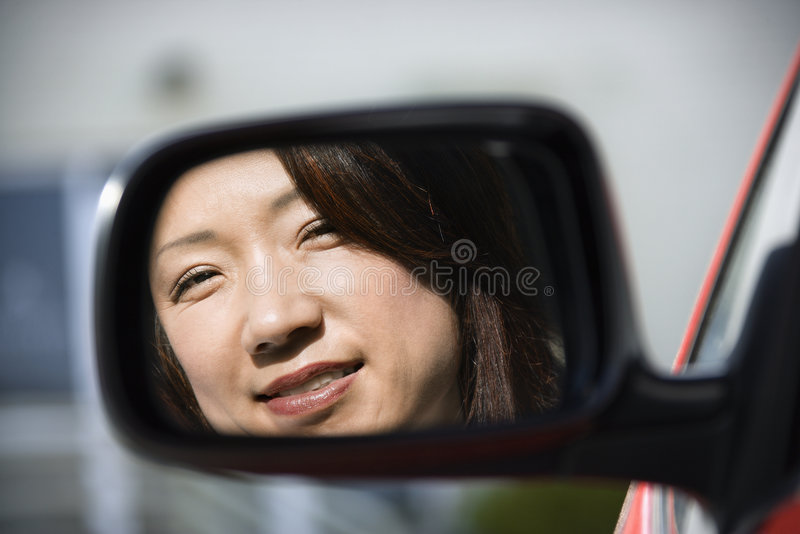 Glimlachende vrouw in autospiegel royalty-vrije stock afbeelding