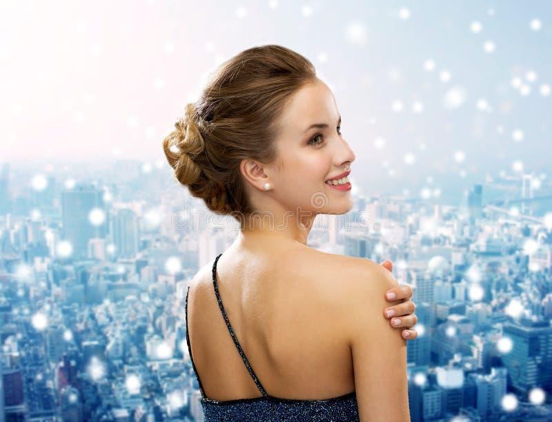 Glimlachende vrouw in avondjurk die oorringen dragen stock fotografie