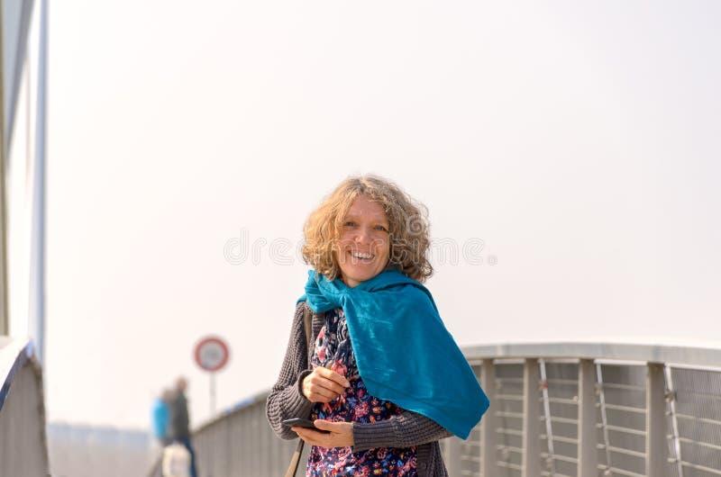 Glimlachende vrouw in blauwe sjaal op de brug stock foto's