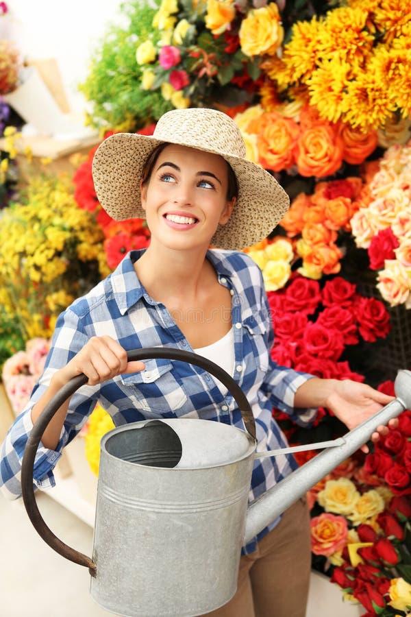 Glimlachende vrouw, bloemist met gieter onder de bloemen royalty-vrije stock fotografie