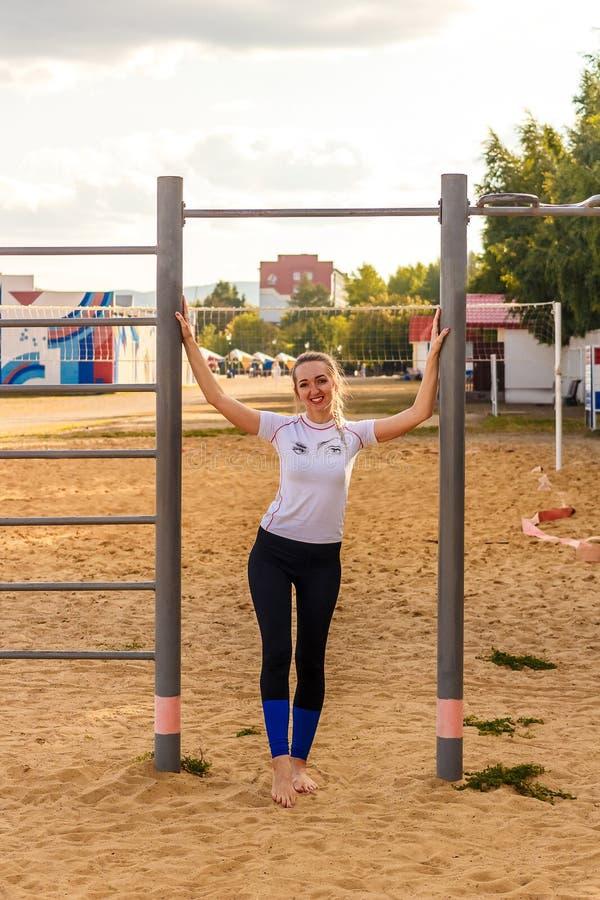 Glimlachende vrouw blootvoets in de strakke tribunes van sportenlegging op het gele zand royalty-vrije stock foto
