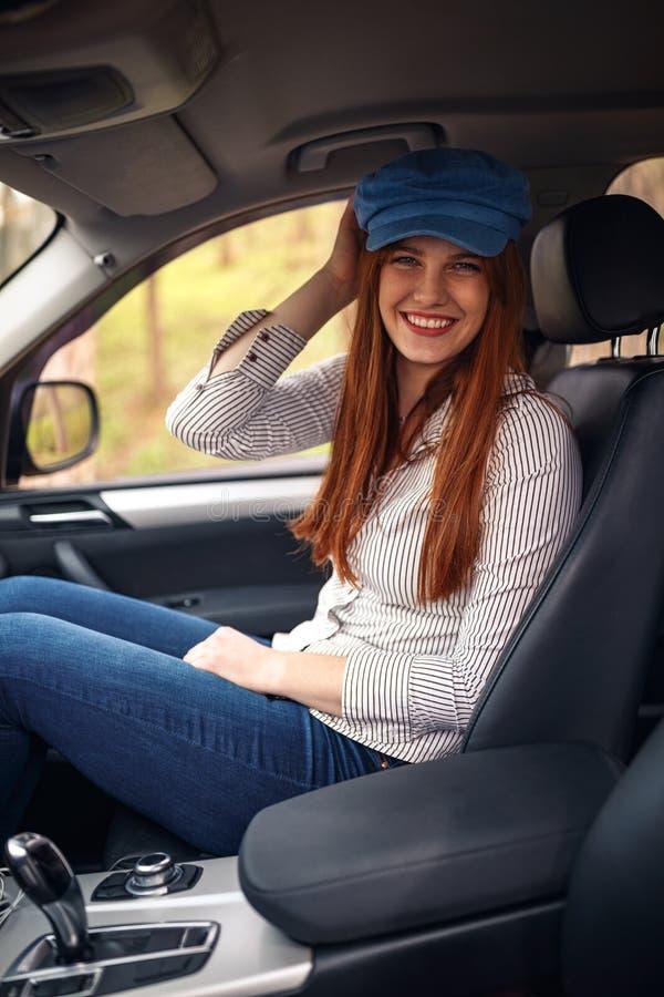 Glimlachende vrouw in de auto die in wegreis en het hebben van pret genieten van stock foto's
