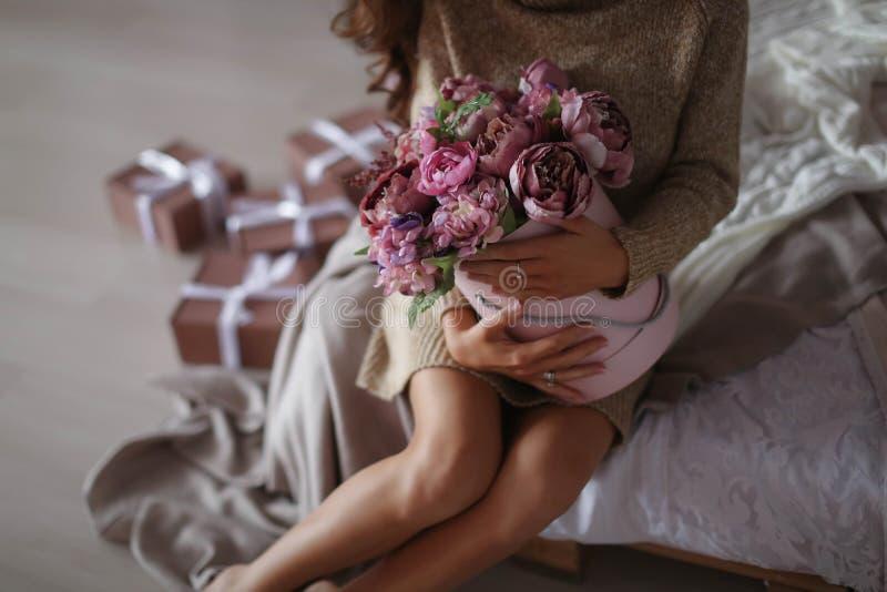 Glimlachende vrouw in de giftdoos van de pyjamaholding en het bekijken de camera, het concept van de valentijnskaartendag royalty-vrije stock afbeeldingen
