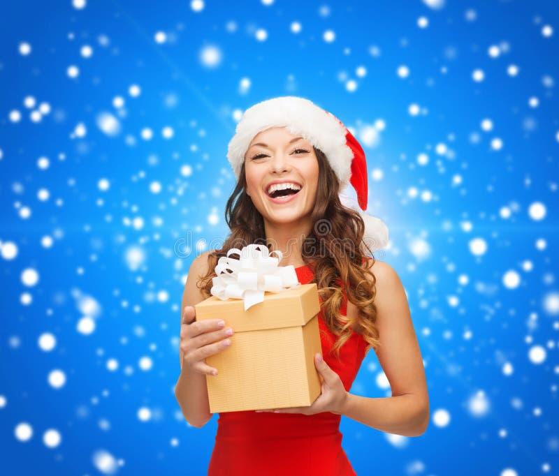Glimlachende vrouw in de hoed van de santahelper met giftdoos royalty-vrije stock fotografie