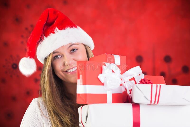 Glimlachende vrouw in de holdingsstapel van het santakostuum Kerstmisgiften royalty-vrije stock foto's