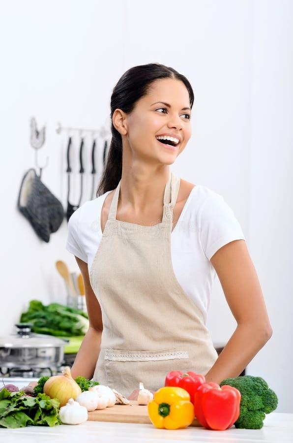 Glimlachende vrouw in de keuken stock fotografie