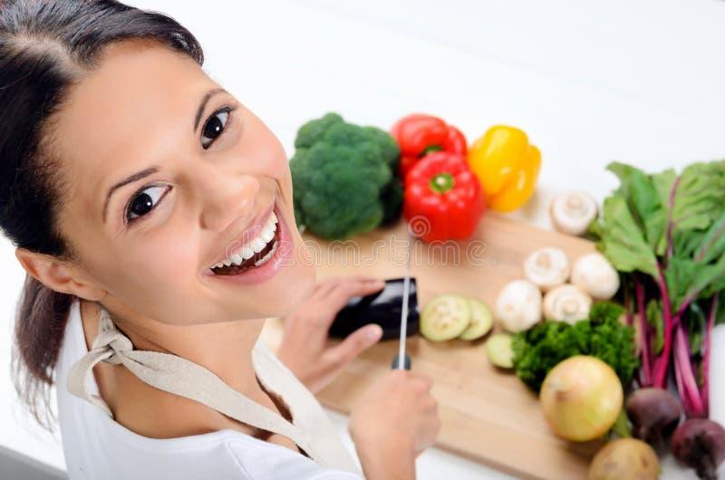Glimlachende vrouw in de keuken stock afbeeldingen