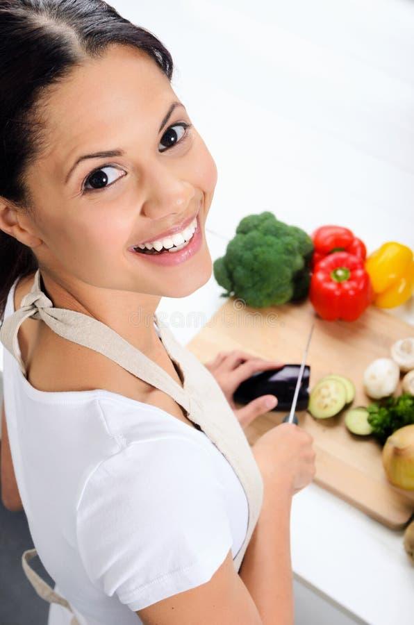 Glimlachende vrouw in de keuken stock foto