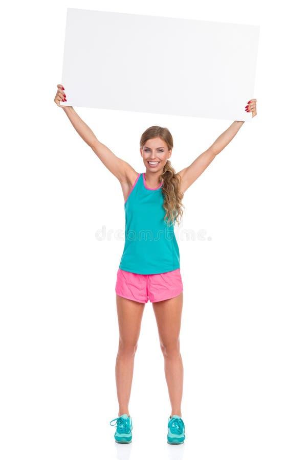 Glimlachende Vrouw in de Trillende Lege Banner van de Klerenholding boven Hoofd royalty-vrije stock afbeelding