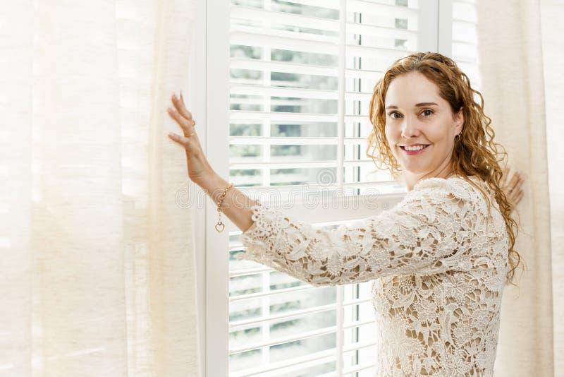 Glimlachende vrouw dichtbij venster royalty-vrije stock foto's