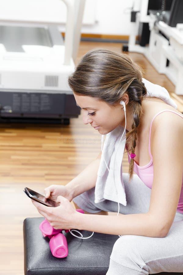 Glimlachende vrouw die aan muziek bij de gymnastiek luisteren stock fotografie