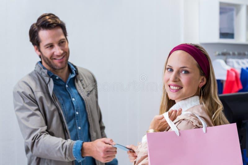 Glimlachende vrouw die achtercreditcard krijgen stock fotografie