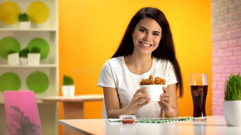 Glimlachende vrouw die beschikbare kom met knapperige gebraden kip houden, die van maaltijd genieten stock afbeelding