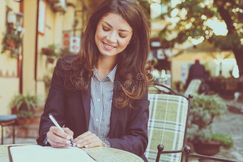 Glimlachende vrouw die bij koffie werken Sluit omhoog royalty-vrije stock foto